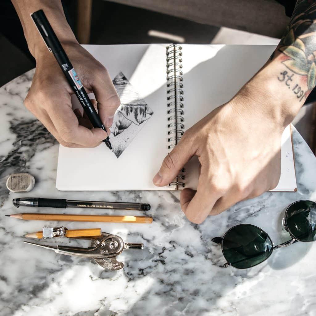Homme en train de dessiner sur un carnet de croquis